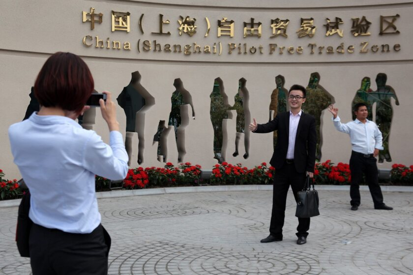 People have souvenir photos taken in front of the entrance to the Shanghai pilot free-trade zone in Shanghai on Sunday.