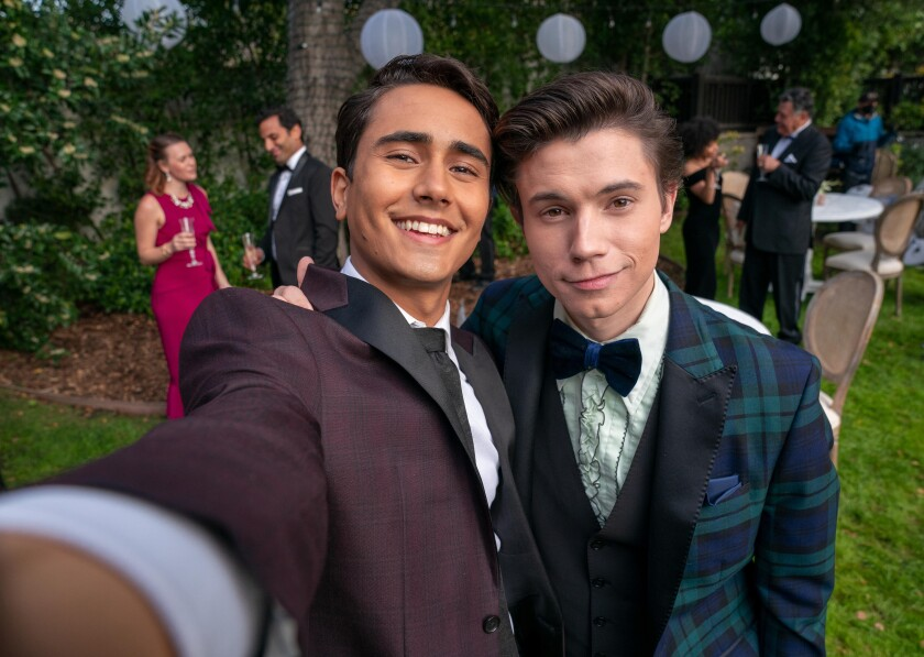 Two men in suits take a selfie.