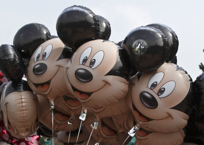 FILE - This May 12, 2015 file photo shows Mickey Mouse balloons at Disneyland Paris, in Chessy, France, east of Paris. Disney is allaying concerns about cord-cutting after reporting better-than-expected revenue in the cable-network division that houses ESPN. Disney said Thursday, Nov. 5, 2015, that
