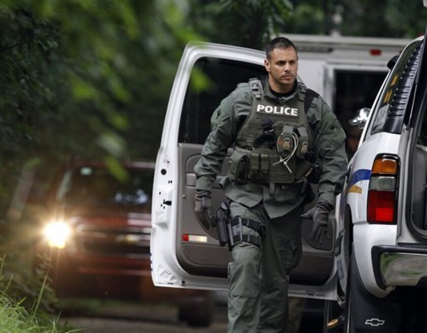 A police officer walks near vehicles on Renninger Road in Douglass Township, Pa., as he arrives near the scene of a fatal shooting Sunday, July 3, 2011. A shooting at a rural home on Renninger Road in suburban Philadelphia killed two people, including a child, and injured three others, authorities said Sunday. A manhunt is under way for the shooter. (AP Photo/Jacqueline Larma)