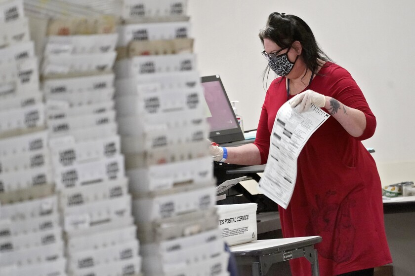 In this Nov. 6 photo, an election worker counts ballots inside the Maricopa County Recorder's Office in Phoenix.