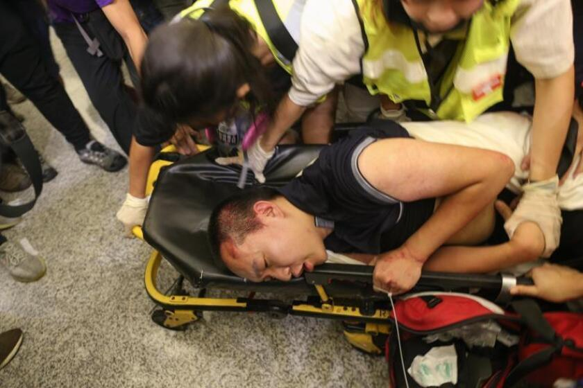 An injured man whom protesters accused of being an undercover police officer is being taken by medical personal after clashes with anti-government protesters at Hong Kong Chek Lap Kok International Airport, Hong Kong, China. EFE/EPA/Jerome Favre