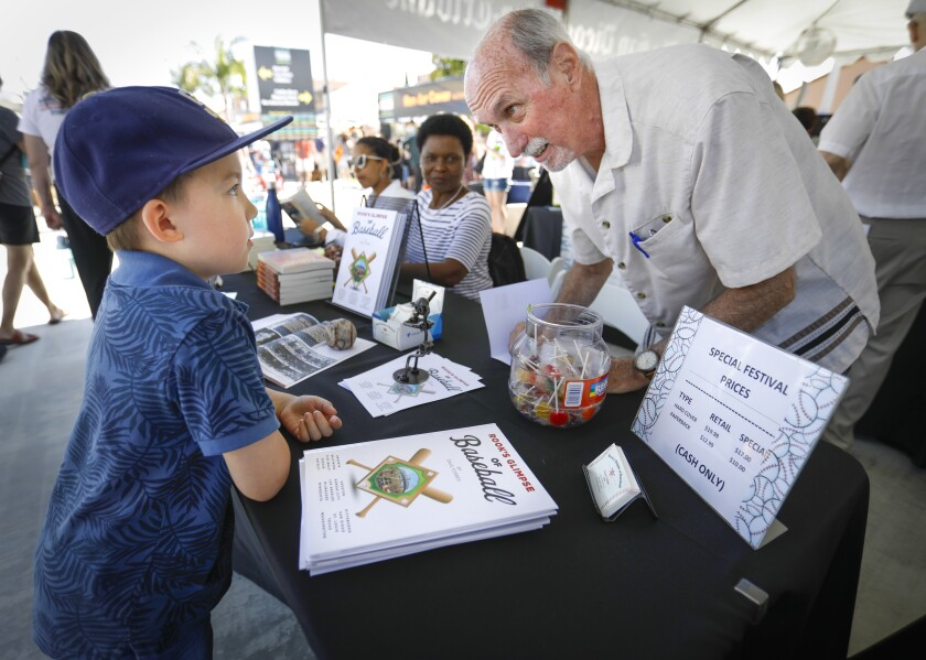 Nine-year-old Jayden Montgomery, left, talks with Dave Forbes, right, author of Rook's Glimpse of Baseball, during The San Diego Union-Tribune Festival of Books at Liberty Station on Saturday.