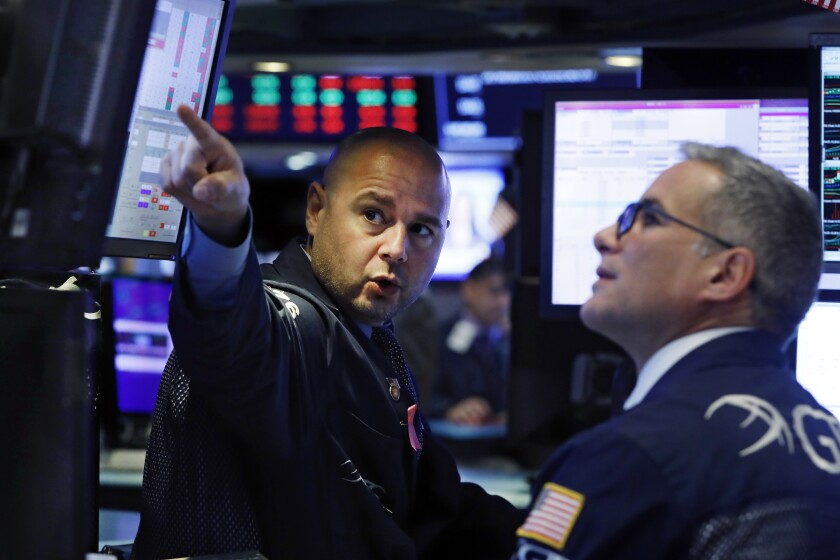 FILE - In this Oct. 7, 2019, file photo specialists Mario Picone, left, and Anthony Rinaldi work on the floor of the New York Stock Exchange. The U.S. stock market opens at 9:30 a.m. EDT on Monday, Oct. 14. (AP Photo/Richard Drew, File)