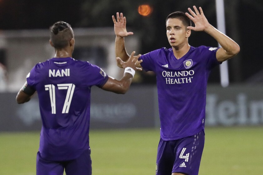 Orlando City defender Joao Moutinho (4) celebrates his goal against LAFC with teammate Nani on Friday evening.