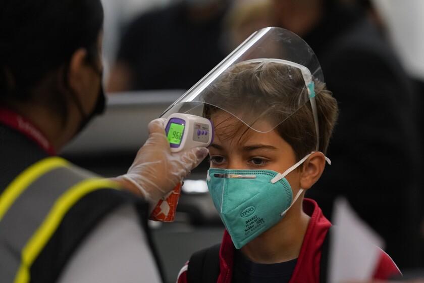 A boy gets his temperature checked