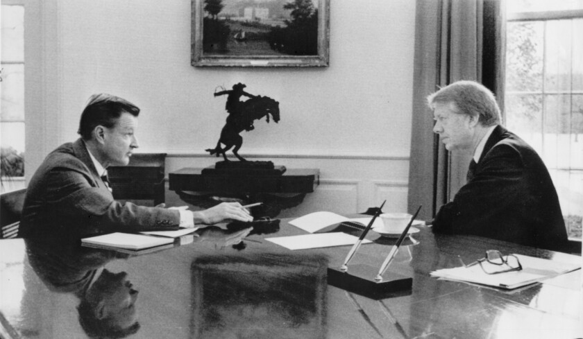 President Carter talks with Zbigniew Brzezinski, his national security advisor, in the Oval Office on January 22, 1977.