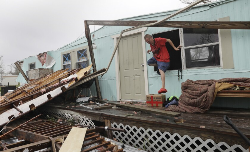 Sam Speights exits a window of his home that was destroyed in the wake of Hurricane Harvey in Rockport, Texas.