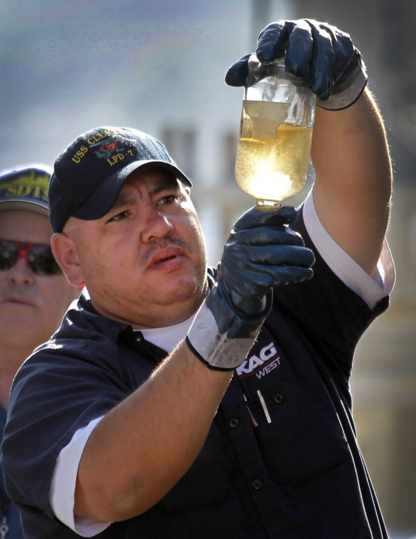 Pedro Garcia checks a sample of algae-based biofuel before it is pumped from a fuel tanker to the Self Defense Test Ship.