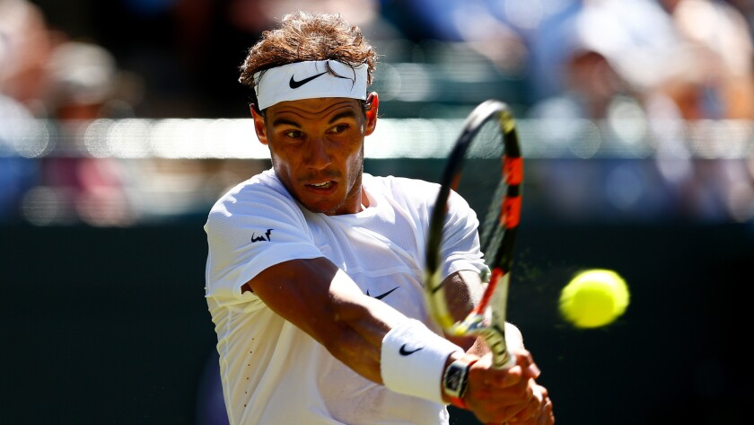 Rafal Nadal hits a return during his first-round match against Thomaz Bellucci at Wimbledon on June 30, 2015.