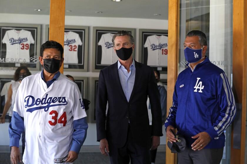 Gov. Gavin Newsom, center, with ex-Dodger pitcher Fernando Valenzuela, left, and California Secretary of State Alex Padilla.