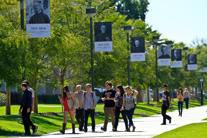 Students walk between classes at Loyola Marymount University under posters of past university presidents.