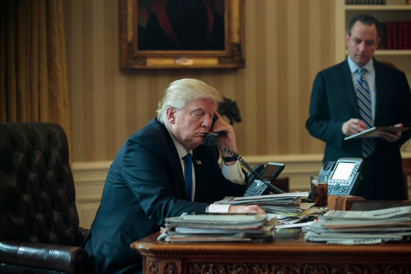 President Trump speaks by phone with Russian President Vladimir Putin in the Oval Office on Saturday as White House Chief of Staff Reince Priebus looks on.