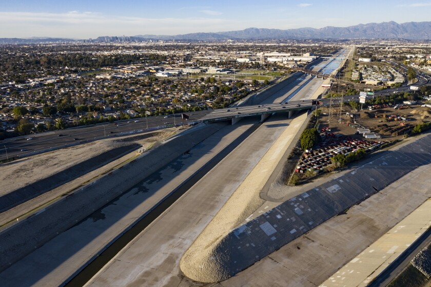 Aerial view of concrete-sided confluence of the Los Angeles River and Rio Honda, with downtown L.A. in the background.