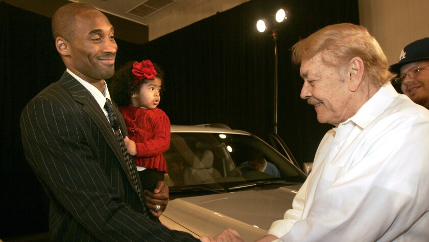 Kobe Bryant shakes hands with Jerry Buss while holding his daughter, Natalia.