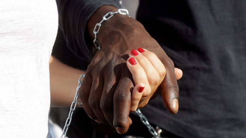 Demonstrators hold hands during a pro-migrants and against racism demonstration, organized by a numb
