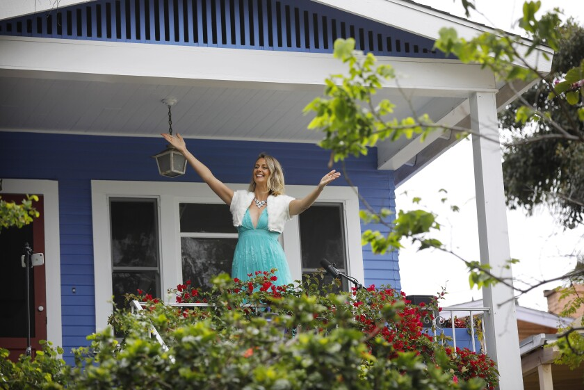Opera singer Victoria Robertson, a soprano, acknowledges a crowd from porch of her North Park home after she sang on April 19, 2020. For the second week in a row, Robertson performed for 15 minutes to a crowd, who kept their distance from each other on the street below.