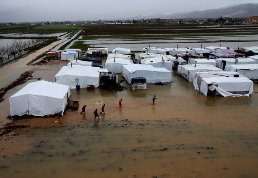 Syrian refugees make their way in flooded water at a refugee camp in the town of Faour near the border with Syria in Lebanon last week.