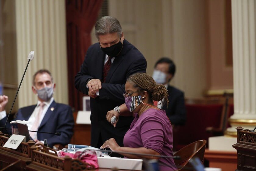 Sen. Holly Mitchell (D-Los Angeles) gets an elbow bump from Sen. Bob Hertzberg (D-Van Nuys).
