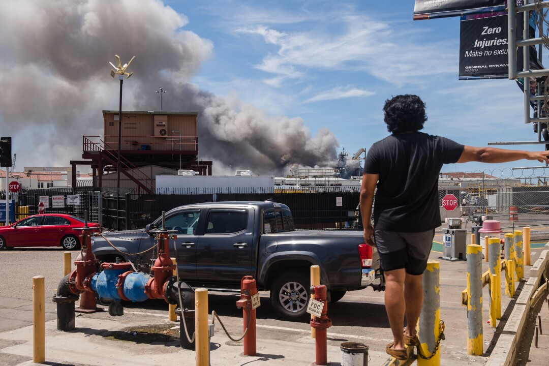A person watches the USS Bonhomme Richard on fire from outside the naval base in San Diego, California on July 12, 2020.