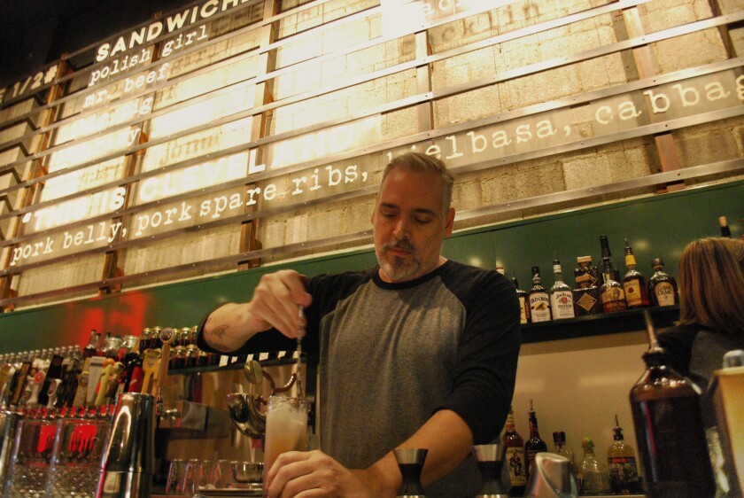A mixologist creates a drink at celebrity chef and native son Michael Symon's restaurant, Mabel's BBQ, in Cleveland.