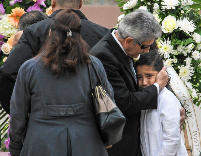Robert Velasco, father of Yvette Velasco, consoles a family member during his daughter's funeral service at Forest Lawn - Covina Hills.