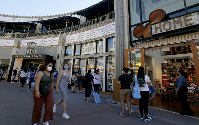 People stroll through the Downtown Disney shopping district in Anaheim in July.