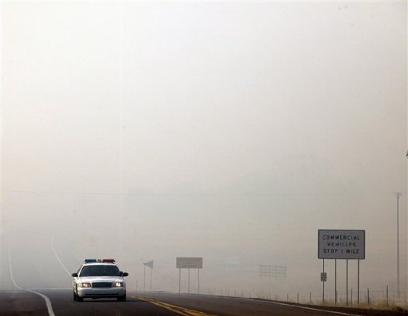 An emergency vehicle is seen as smoke from the Wallow Fire covers highway 60 in Springerville, Ariz., Thursday, June 9, 2011. Several mountain communities have emptied in advance of the fire, and a utility that supplies power to customers in southern New Mexico and west Texas issued warnings of possible power interruptions. (AP Photo/Marcio Jose Sanchez)