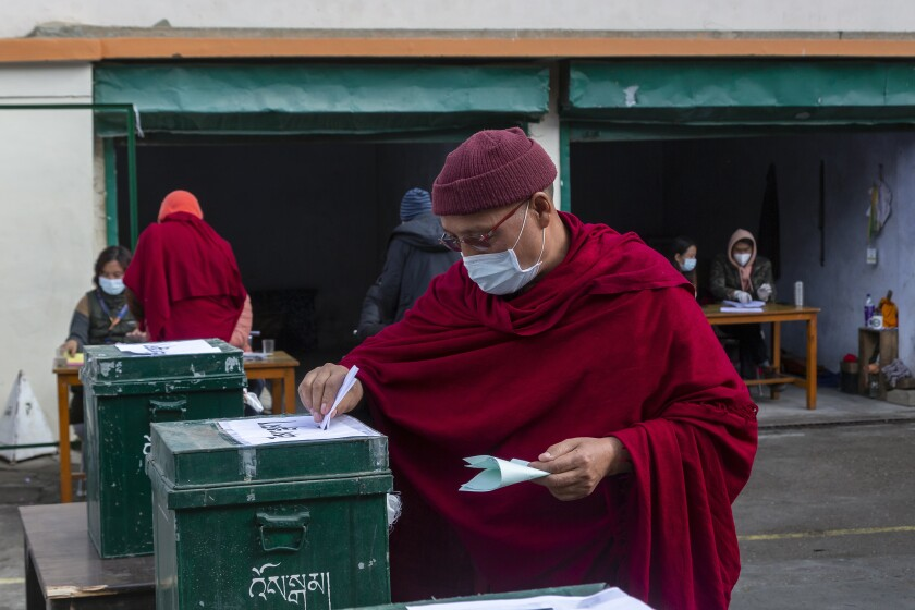 A Tibetan Buddhist monk casts his ballot in Dharmsala, India, on Sunday.