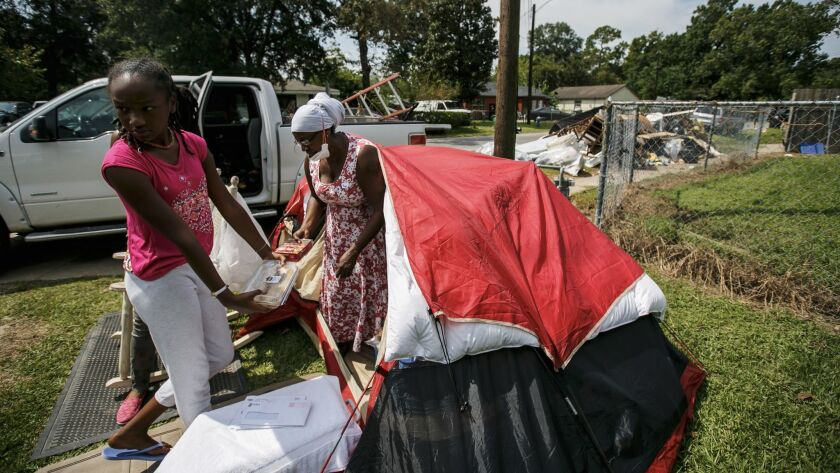 Nikki Fields, center, with daughter Rayven outside their damaged Houston home.