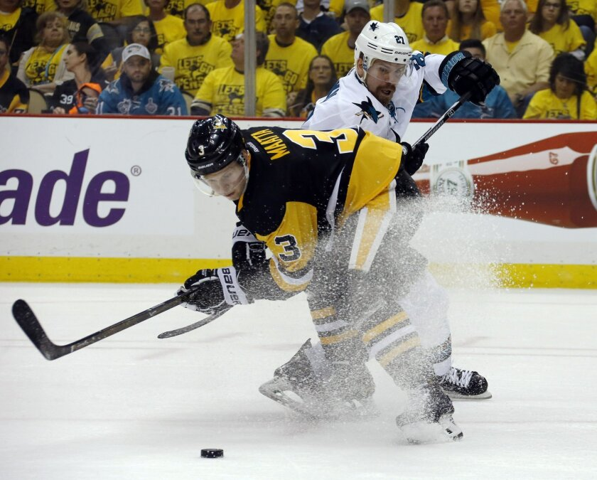 Pittsburgh Penguins' Olli Maatta (3) and San Jose Sharks' Joonas Donskoi, rear, battle for the puck during the second period in Game 1 of the Stanley Cup final series Monday, May 30, 2016, in Pittsburgh. (AP Photo/Keith Srakocic)