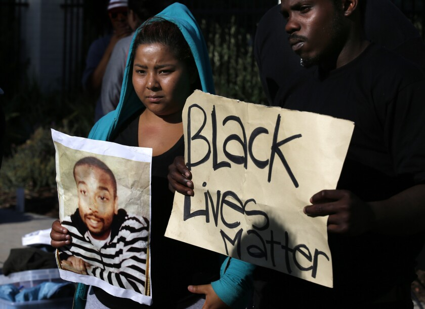 Activists with Black Lives Matter holding a photograph of Ezell Ford, who was killed by L.A. police officers in 2014. Members of the group have protested the policies of Dist. Atty. Jackie Lacey, and on Monday showed up at her house, where they were confronted by her husband wielding a gun.