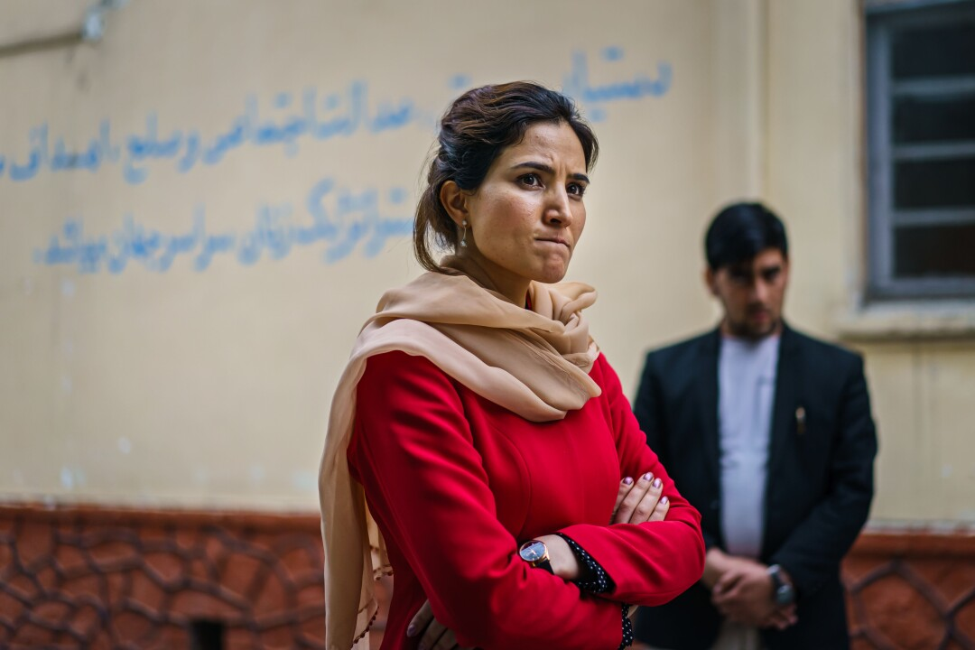 Hosna Jalil, arms folded, talks to staff members