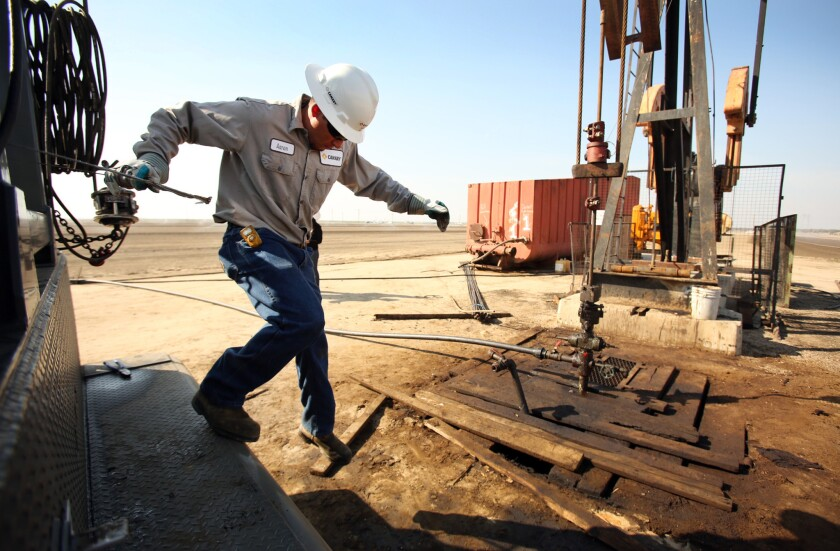 Aaron Kent, an employee of oil services firm Canary, works at an oil rig pump jack near Bakersfield in March 2013. Some 12,000 people are on oil and gas extraction and well-drilling payrolls in the area.