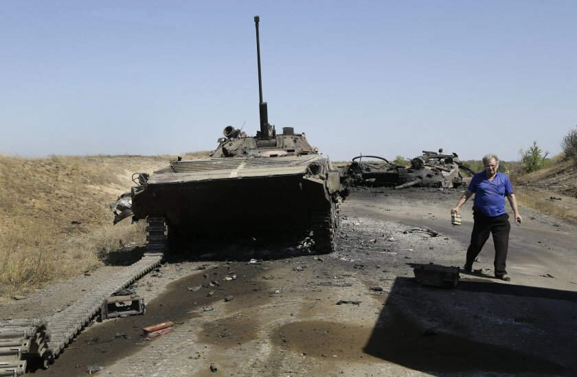A column of destroyed Ukrainian military vehicles are seen near the village of Novokaterynivka, eastern Ukraine, Tuesday, Sept. 2, 2014. Ukrainian troops have over the past week suffered a string of major military losses in their offensive against Russian-backed separatist rebels, losing large swathes of territory and having hundreds of soldiers captured. (AP Photo/Sergei Grits)