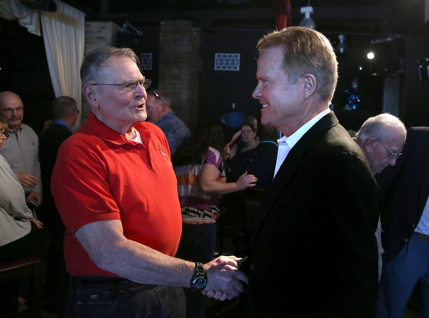 Former U.S. Sen. Jim Webb (right) greets an attendee during a fundraiser for Iowa House Democrats on April 12 in Mason City, Iowa. The former senator is considering a run for president.