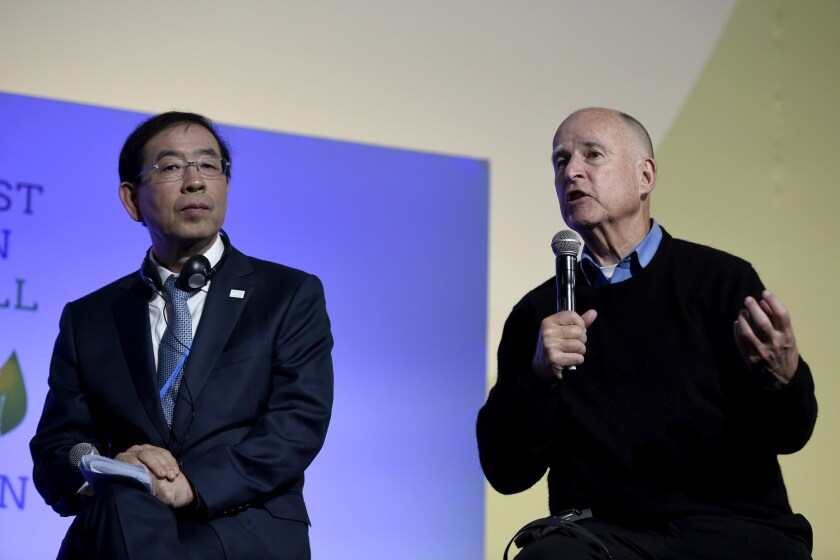 Seoul Mayor Park Won-soon listens to Gov. Jerry Brown at a working session of the United Nations conference on climate change in Le Bourget, France, on Dec. 5.