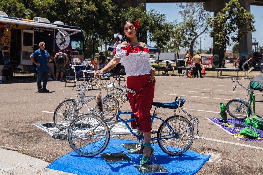 Julia Orozco posa en una bicicleta lowrider durante el evento de Open House en Chicano Park