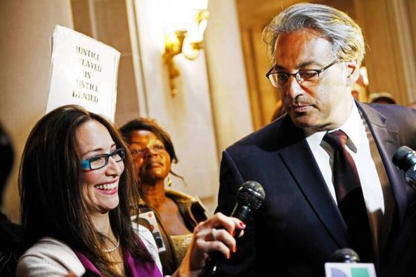 San Francisco Sheriff Ross Mirkarimi and his wife, Eliana Lopez, are surrounded by media during a break in a San Francisco Ethics Commission hearing.