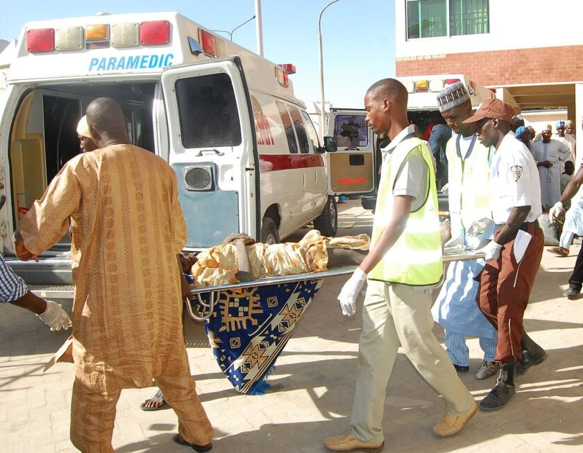 Rescue workers transport a victim of a suicide bomb attack at a refugee for treatment at a hospital, in  Maiduguri, Nigeria, Wednesday, Feb. 10, 2016. Two female suicide bombers blew themselves up in a northeast Nigerian refugee camp, killing at least 56 people, health and rescue officials said Wed