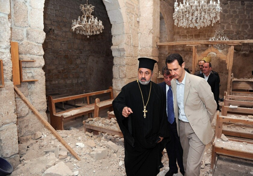 A picture from the official Syrian Arab News Agency shows President Bashar Assad, center right, looking at the damaged interior of a monastery in the ancient Christian town of Maaloula, which his troops recently recaptured from rebels.