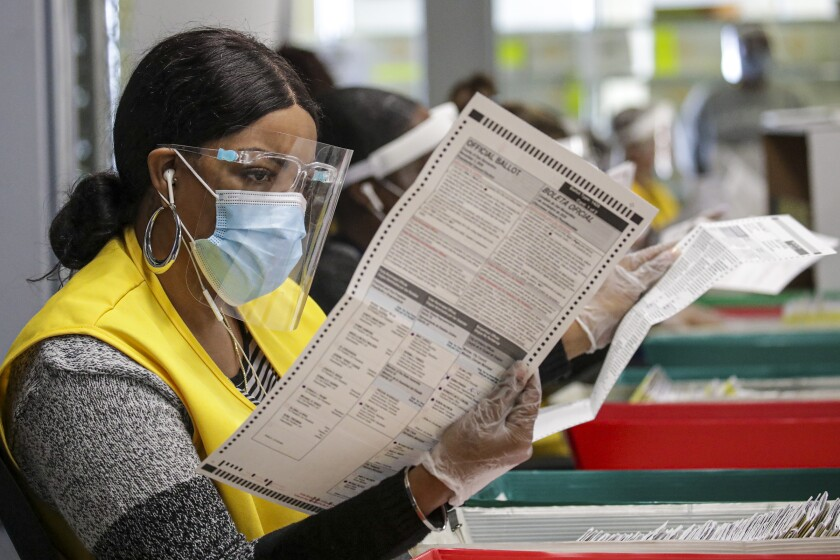 A woman in a face shield and mask looks over a printed paper ballot