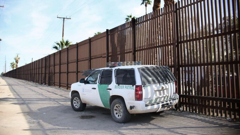 A Border Patrol agent looks over the wall in Calexico. A barrier built in the 1990s from recycled metal scraps and landing mat will be torn down for bollard-style posts that are 30 feet high.