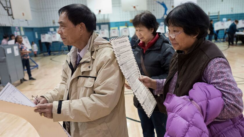 Zhou Nan Zhou, left, his wife, Li Li Tan, and their friend, Yulsman Yang -- all originally from China -- wait to cast their ballots Tuesday in New York City.