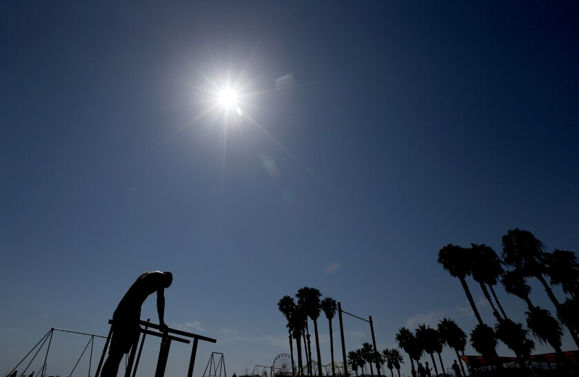 A man pauses from working out under the hot sun on Santa Monica Beach on Saturday.