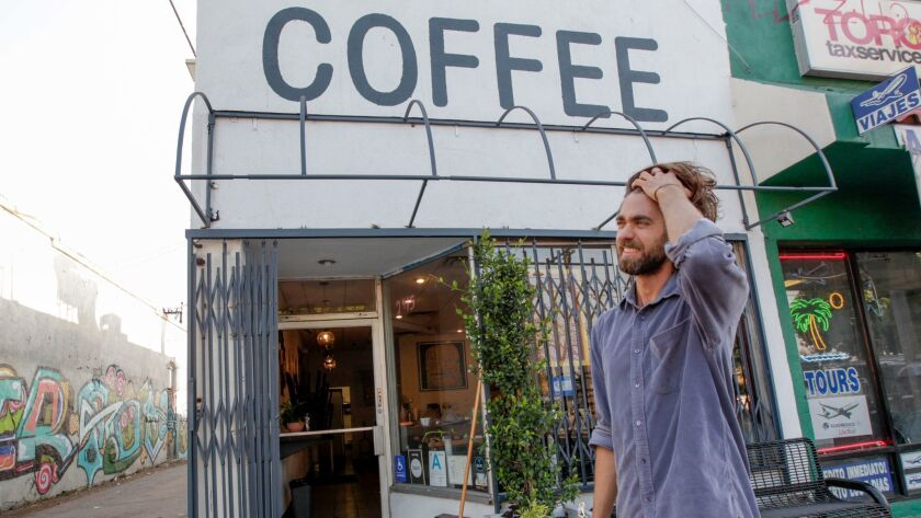 John Schwarz, co-owner of Weird Wave Coffee, assesses damage caused by someone who may have thrown a rock at the glass door of the coffee shop on July 19. The business has been the target of anti-gentrification protests since it opened mid-June.
