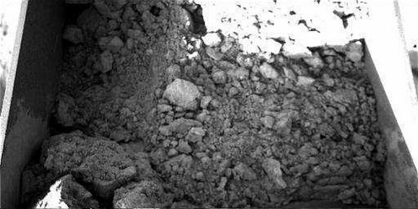 The lander's nearly 8-foot-long robotic arm dumped a cup full of clumpy soil atop oven No. 4 — but none of the particles fell through the guard screen into the oven, whose opening is about the thickness of a pencil lead. The clumpiness could be caused by any of several factors, including the presence of water. NASA released this photo today.