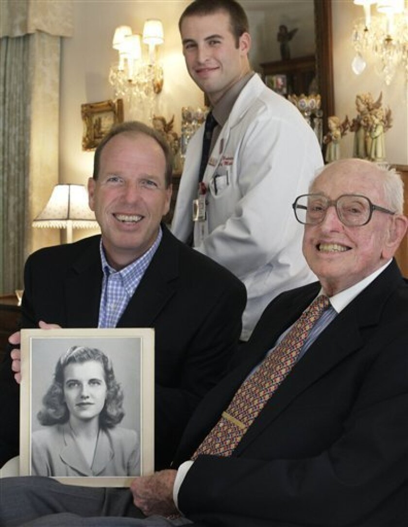 """In this photo taken Sept. 7, 2010 in Munster, Ind., Jim Purcell holds a photo of his late wife of 64 years, Dorothy """"Dot"""" Purcell, in his living room accompanied by his his son Mike Purcell, left, and Indiana University Northwest first-year medical student Lucas Buchler. Dot Purcell wanted her body to go to science and she ended up at Buchler's school, which has an unusual program where medical students often meet the families of the donors they dissect in gross anatomy. Though reluctant at first, some of Purcell's family members, including her husband, ended up meeting Buchler and developing a friendship with him and a few other students. (AP Photo/M. Spencer Green)"""