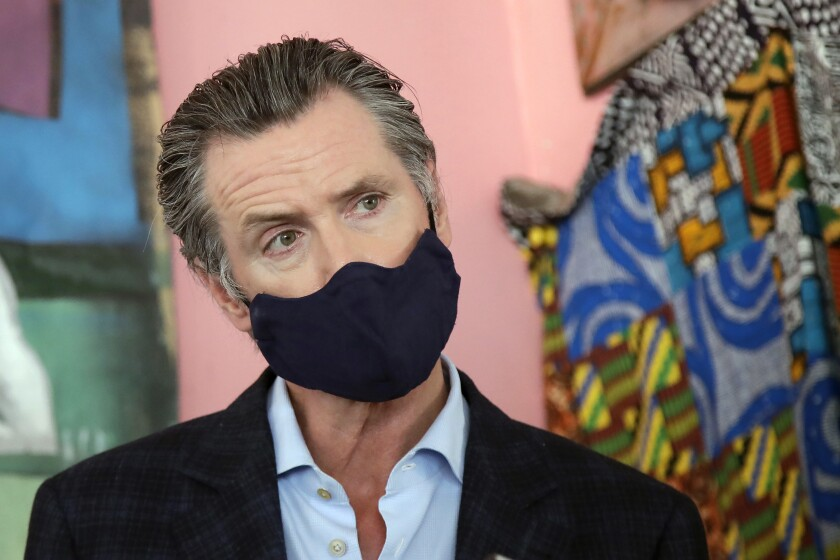 California Gov. Gavin Newsom wears a protective mask on his face