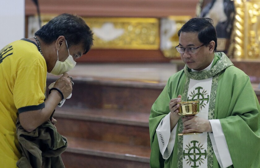 In this Feb. 10, 2020, photo, Catholic priest Fr. Joseph Arellano, right, looks at a man who forgot to take off his protective mask and tried to insert the host in his mouth during communion at a mass at the Minor Basilica of San Lorenzo Ruiz in Manila's Chinatown, Philippines. In a popular Catholic church in Manila, nearly half of the pews were empty for Sunday Mass. The few hundred worshippers who showed up, some in protective masks, have been asked to refrain from shaking or holding hands in prayers. (AP Photo/Aaron Favila)